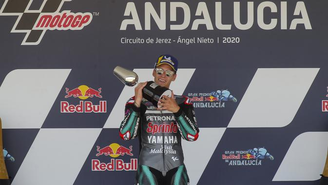 Pembalap Petronas Yamaha, Fabio Quartararo, merayakan kemenangan di atas podium usai menjuarai MotoGP Andalusia di Sirkuit Jerez, Minggu (26/7/2020). Fabio Quartararo berhasil finis pertama dengan catatan waktu 41 menit 22,666 detik. (AP Photo/David Clares)