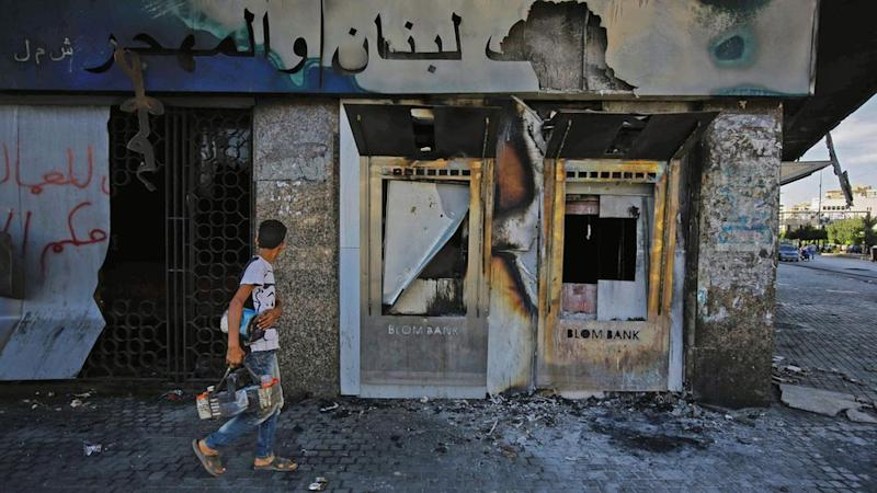 A youth walks past a burnt-down branch of a Lebanese bank in al-Nour Square in Tripoli, Lebanon (12 June 2020)