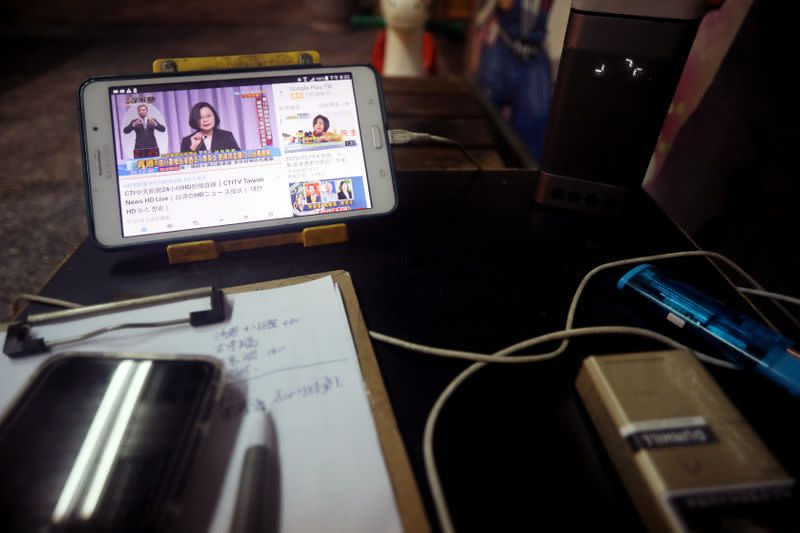 Taiwan President Tsai Ing-wen is seen on a phone screen during the third live policy address ahead of January's election, in Tainan
