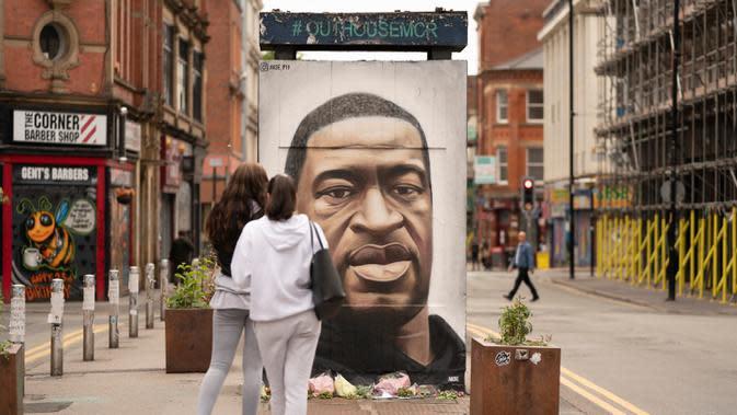 Warga mengamati mural George Floyd di Manchester tengah, Inggris (4/6/2020). George Floyd tewas kehabisan napas saat dalam penahanan pihak kepolisian Negara Bagian Minnesota, wilayah Midwest Amerika Serikat, pada pekan lalu. (Xinhua/Jon Super)