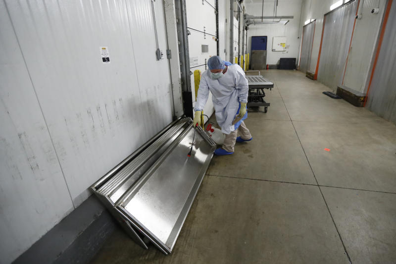 In this Tuesday, May 5, 2020, photo, a member of the Illinois National Guard sanitizes a body tray on the loading dock of the Cook County Medical Examiner's auxiliary surge storage center after an emergency-management truck arrived with half-a-dozen bodies in Chicago. Incoming bodies to the surge center, with a capacity to hold 2,000 bodies, are taken to one of three rooms with the combined square footage of a football field. (AP Photo/Charles Rex Arbogast)