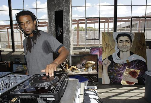 "In this Oct. 23, 2012 photo, Kent Morrison known as DJ Relentless prepares for an upcoming performance at Cueto James Art Gallery, for the opening of show titled ""Uriel Landeros: Houston We Have a Problem"" in Houston. Uriel Landeros, is the man accused of vandalizing a Picasso painting at the Menil with spray paint in June. The work in the background is not by Landeros. (AP Photo/Houston Chronicle, Melissa Phillip)"