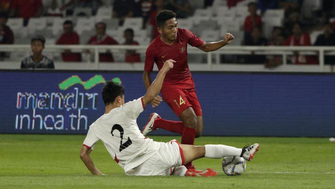 Striker Timnas Indonesia U-19, Fajar Fathur, berebut bola dengan pemain Timnas Korea Utara pada laga Kualifikasi AFC U-19 2020 di Stadion GBK, Jakarta, Minggu (10/11). Indonesia U-19 berhasil menahan imbang 1-1 DPR Korea. (Bola.com/Yoppy Renato)
