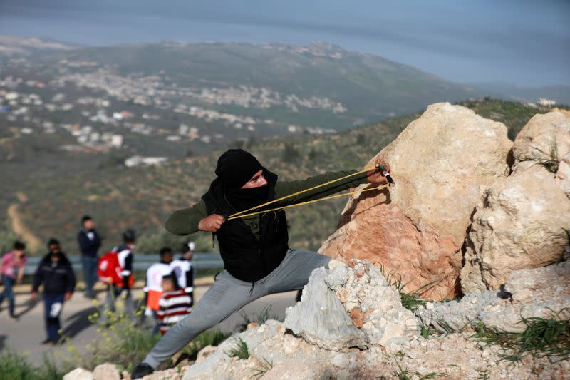 A Palestinian demonstrator uses a slingshot to hurl stones at Israeli forces during a protest against Israeli settlements, near the town of Beita in the Israeli-occupied West Bank