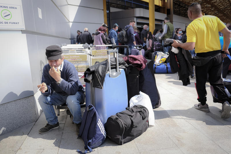 Romanian seasonal workers wait outside the Avram Iancu international airport, in Cluj, central Romania, Thursday, April 9, 2020. More then 1800 workers from across Romania are traveling on 12 flights to Berlin, Baden Bade and Dusseldorf in Germany, most of them to work in asparagus farms. (AP Photo/Raul Stef)
