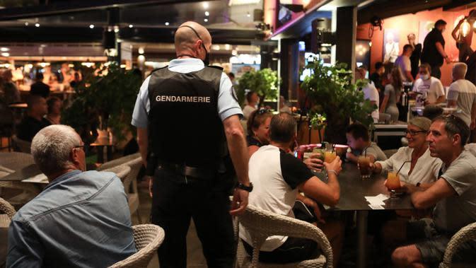 Polisi Prancis berpatroli di sebuah bar untuk mengontrol penggunaan masker di jalan-jalan Argeles-sur-Mer, Rabu (13/8/2020). Pemakaian masker di beberapa area ramai di sekitar Paris merupakan kewajiban sebagai upaya untuk membendung peningkatan tajam infeksi covid-19. (RAYMOND ROIG/AFP)