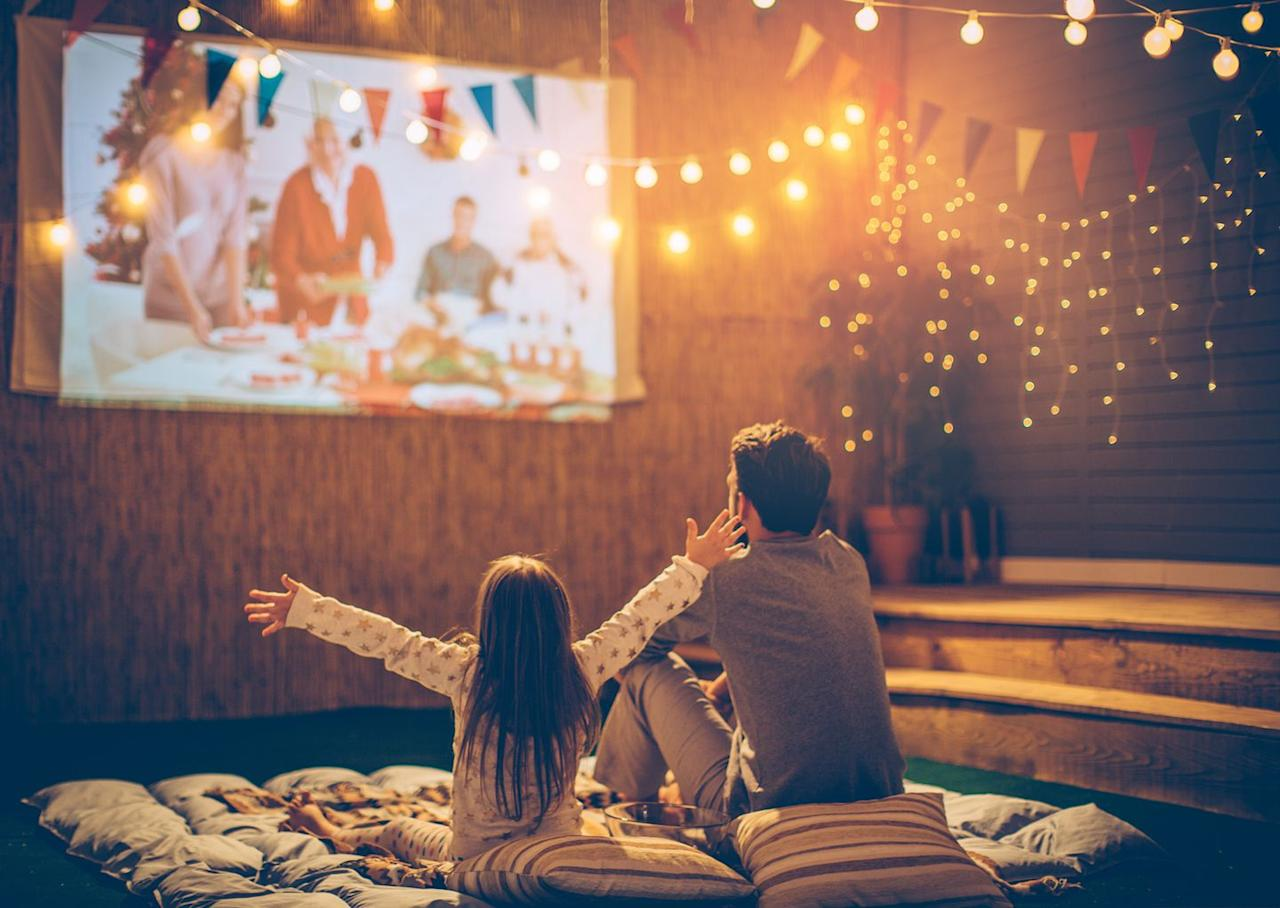 """<p>Put those extra blankets stuffed in your linen closet to good use. Hang a large white bed sheet from your fence to re-create a big screen. Make a palette on the ground with all the extra fluff, and settle in under the stars as you and your family watch these <a href=""""https://www.countryliving.com/life/entertainment/g20956684/kids-movies-on-netflix/"""" target=""""_blank"""">classic kids movies</a>.</p><p><a class=""""body-btn-link"""" href=""""https://www.amazon.com/Projector-Jinhoo-Supported-Lifetime-Compatible/dp/B07MHYSNRJ/?tag=syn-yahoo-20&ascsubtag=%5Bartid%7C10050.g.2633%5Bsrc%7Cyahoo-us"""" target=""""_blank"""">SHOP PROJECTORS</a></p>"""