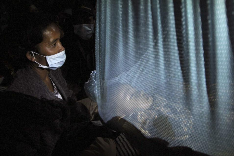 A mother sits near her baby at an evacuation centre at Tiga Ndreket village in Karo district