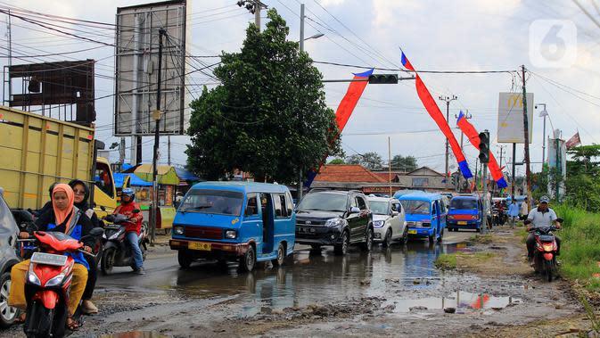 Kondisi Jalan Raya Bojonggede yang sudah berlubang sejak berbulan-bulan lalu, Kec. Bojonggede, Bogor, Jawa Barat, Sabtu (22/2/2020). Masyarakat sekitar dekat jalan berlubang mengeluhkan karena hingga saat ini jalananan belum juga di perbaiki. (merdeka.com/Magang/Muhammad Fayyadh)