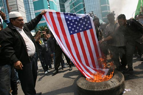 "Indonesian Muslims burn an American flag during a protest against an American-made film that ridicules Prophet Muhammad outside the U.S. Consulate in Medan, North Sumatra, Indonesia, Tuesday, Sept. 18, 2012. Indonesians continue to protest the anti-Islam film ""Innocence of Muslims,"" torching the flag and tires outside the consulate in the country's third largest city of Medan. (AP Photo/Binsar Bakkara)"
