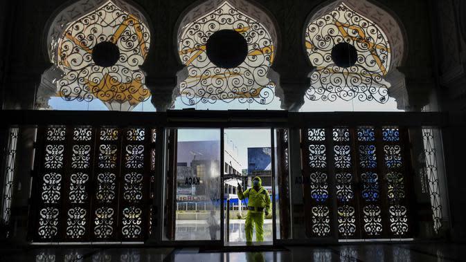Polisi menyemprotkan cairan disinfektan di Masjid Agung Baiturrahman, Banda Aceh, Indonesia, 20 Maret 2020. Hingga 21 Maret 2020 siang, jumlah pasien positif virus corona COVID-19 di Indonesia telah mencapai 450 orang, 38 meninggal. (Photo by CHAIDEER MAHYUDDIN/AFP)