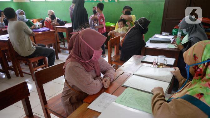 Wali murid siswa Sekolah SD kelas 4,5 dan 6 sedang mengambil rapot secara bergilir di Sekolah Islam Raudlatul Hikmah, Parakan, Pondok Benda, Pamulang, Tangerang Selatan, Banten, Jumat (16/10/2020). (merdeka.com/Dwi Narwoko)