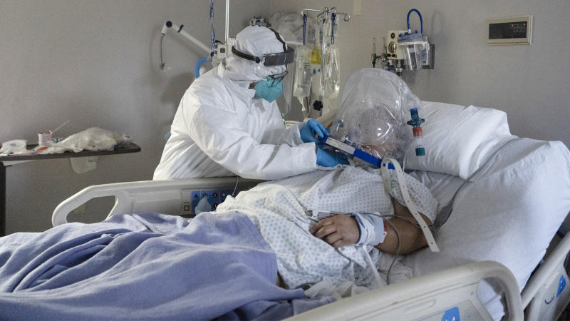 A member of the medical staff treats a patient wearing helmet-based ventilator in the COVID-19 intensive care unit at the United Memorial Medical Center in Houston. (Go Nakamura/Getty Images)