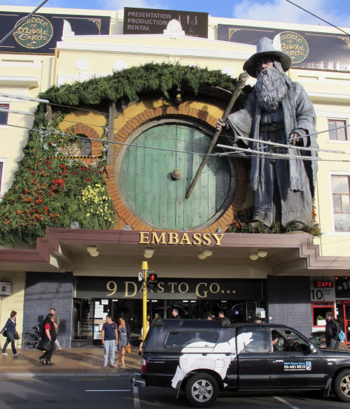 "People walk by the Embassy Theater where a giant statue of the character Gandalf from the upcoming movie ""The Hobbit: An Unexpected Journey"" overlooks the passersby in Wellington, New Zealand, Monday, Nov. 19, 2012. Animal wranglers involved in the making of ""The Hobbit"" movie trilogy say the production company is responsible for the deaths of up to 27 animals, largely because they were kept at a farm filled with bluffs, sinkholes and other ""death traps."" (AP photo/Nick Perry)"