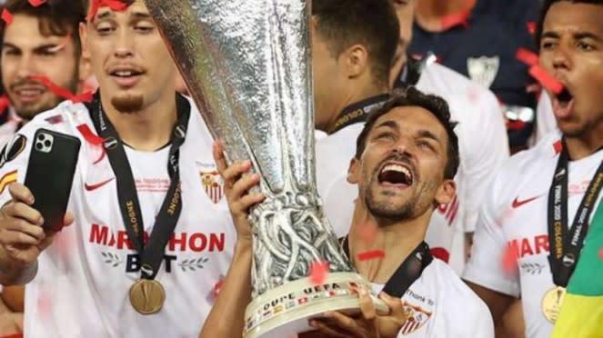 Kapten Sevilla, Jesus Navas mengangkat trofi Liga Europa 2019/20.