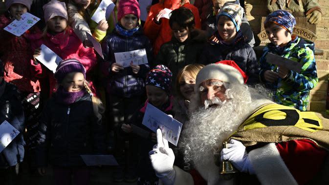 Seorang pria berpakaian Santa Claus berpose bersama anak-anak saat pembukaan kantor pos Sinterklas di Himmelpfort, Jerman, Kamis (14/11/2019). Anak-anak di seluruh dunia mulai mengirim surat berisi permohonan kepada sinterklas di kantor pos itu. (Tobias SCHWARZ / AFP)
