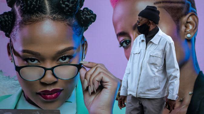 Seorang pria yang mengenakan masker berdiri di depan papan iklan produk rambut di Soweto, Afrika Selatan, Senin (29/6/2020). (AP Photo/Themba Hadebe)