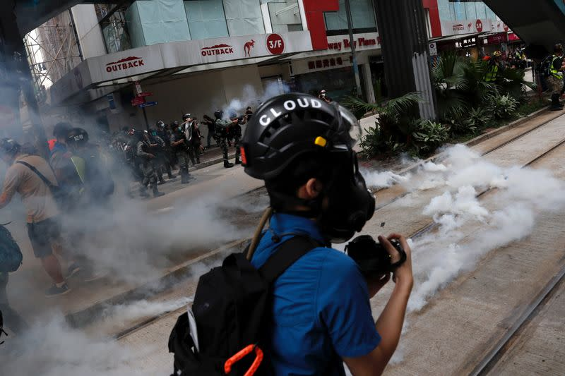 Riot police fire tear gas to disperse anti-government protesters during a march against Beijing's plans to impose national security legislation in Hong Kong