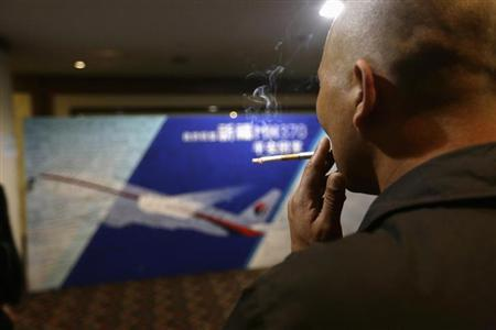 A family member of a passenger onboard Malaysia Airlines Flight MH370 smokes in front of a message board dedicated to passengers onboard the missing Malaysia Airlines Flight MH370 at Lido Hotel, in Beijing March 24, 2014. REUTERS/Jason Lee