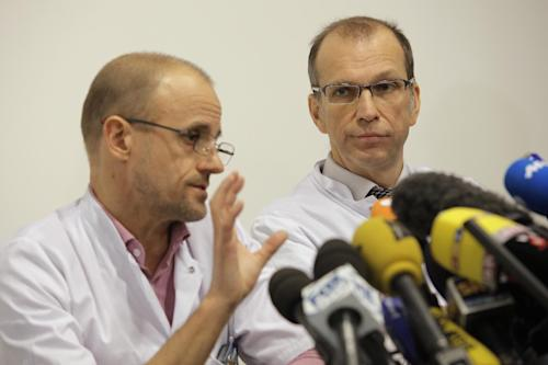"Professor Jean-Francois Payen, left, and Emmanuel Gay, right, answer questions from journalists during a press conference at the Grenoble hospital, in the French Alps, where former seven-time Formula One champion Michael Schumacher is being treated after sustaining a head injury during a ski accident in Meribel, France, Tuesday, Dec. 31, 2013. Doctors treating Michael Schumacher refused Monday to predict the outcome for the former Formula One driver, saying they were taking his very critical head injury ""hour by hour"" following his ski accident. Chief anesthesiologist Jean-Francois Payen told reporters that the seven-time champion is still in a medically induced coma. (AP Photo/Laurent Cipriani)"