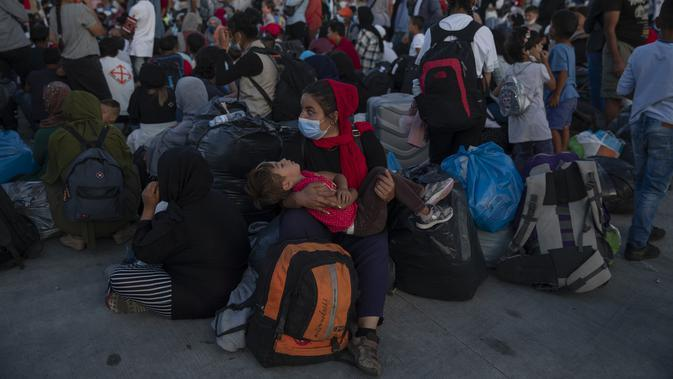 Pengungsi dan migran yang mengenakan masker pelindung untuk membantu mencegah penyebaran virus corona menunggu untuk naik bus setelah mereka tiba di pelabuhan Lavrio, sekitar 75 kilometer (48miles) selatan Athena (29/9/2020). (AP Photo/Petros Giannakouris)