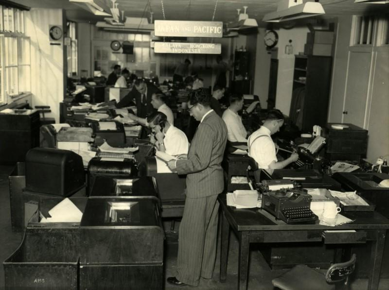 A file photo from the Reuters archive shows journalists working in the Japan and Pacific section at the Reuters building in 1955