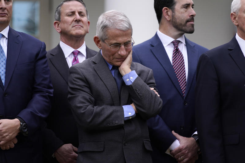 Dr. Anthony Fauci, director of the National Institute of Allergy and Infectious Diseases, center, listens during a news conference about the coronavirus in the Rose Garden of the White House, Friday, March 13, 2020, in Washington. (AP Photo/Evan Vucci)