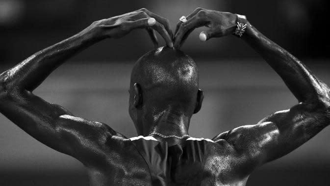 Pelari Inggris, Mo Farah, merayakan kemenangan dengan gaya khasnya 'Mobot' di final lari 10.000m Kejuaraan Dunia Atletik 2015 di Stadion Nasional, Beijing, Tiongkok. (22/8/2015). (AFP Photo/Franck Fife)
