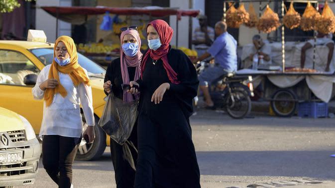 Perempuan Tunisa mengenakan masker untuk melindungi diri dari virus Corona terlihat di sebuah pasar saat kasus baru infeksi melonjak, di kota Gabes, Rabu (27/8/2020). Tunisia pada 25 Agustus 2020 melaporkan peningkatan tertinggi kasus baru Covid-19 dibandingkan minggu sebelumnya. (FETHI BELAID/AFP)
