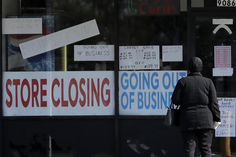 A woman looks at signs at a store closed due to COVID-19 in Niles, Ill., Wednesday, May 13, 2020. (AP Photo/Nam Y. Huh)
