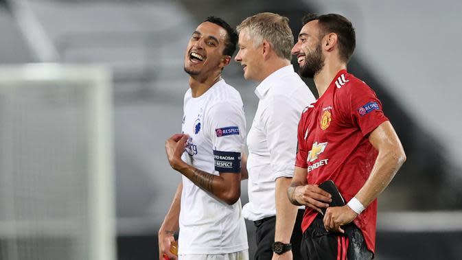 Manajer Manchester United, Ole Gunnar Solskjaer (tengah), berbincang dengan kapten FC Copenhagen, Zeca (kiri), dan Bruno Fernandes, setelah pertandingan Liga Europa di RheinEnergieStadion, Cologne, Selasa (11/8/2020) dini hari WIB. (AFP/Wolfgang Rattay)