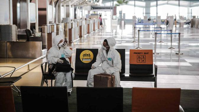 Sejumlah calon penumpang pesawat menggunakan alat pelindung diri (APD) di Terminal 3 Bandara Soekarno-Hatta (Soetta), Tangerang, Banten, Senin (11/5/2020). Calon penumpang menggunakan APD untuk melindungi diri dari penularan virus corona COVID-19. (Liputan6.com/Faizal Fanani)