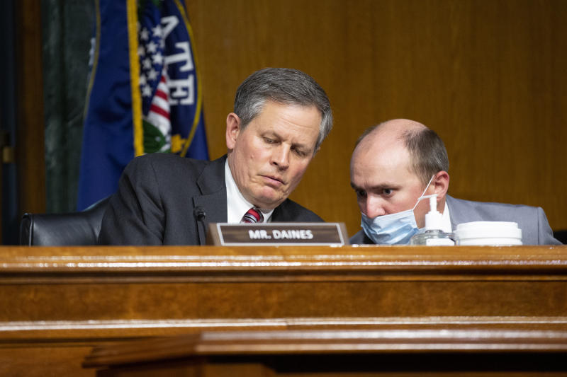 FILE - In this Tuesday, June 2, 2020 file photo Sen. Steve Daines, R-Mont., speaks to a member of his staff during a Senate Finance Committee hearing on the FDA foreign drug manufacturing inspection process on Capitol Hill in Washington. Daines is seeking a second term and faces Montana Gov. Steve Bullock in the Nov. 3, 2020 election. (Stefani Reynolds/Pool via AP,File)