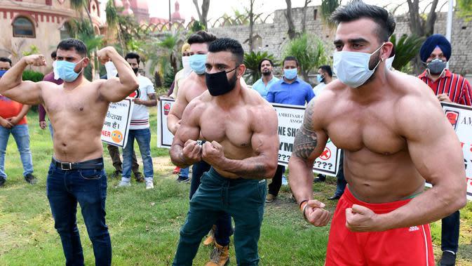 Pemilik dan pelatih gym memamerkan otot mereka saat protes menuntut pemerintah membuka kembali pusat kebugaran di Amritsar, India, Minggu (7/6/2020). Mereka meminta aktivitas tempat olahraga gym juga diizinkan buka setelah pelonggaran lockdown, bukan hanya kegiatan perekonomian. (NARINDER NANU/AFP)