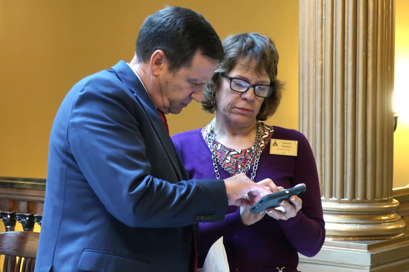 Kansas state Sen. Dennis Pyle, left, R-Hiawatha, consults with Jeanne Gawdun, right, a Kansans for Life lobbyist, following a meeting of GOP senators about a proposed amendment to the state constitution on abortion, Wednesday, Jan. 29, 2020, at the Statehouse in Topeka, Kan. The amendment would overturn a Kansas Supreme Court decision protecting abortion rights, and critics say it could lead eventually to a ban on abortion. (AP Photo/John Hanna)