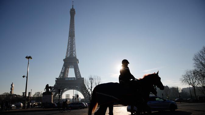 Seorang petugas polisi berpatroli di dekat Menara Eiffel di Paris, Senin (30/12/2019). Pemerintah Prancis akan mengerahkan 100.000 petugas polisi untuk mengamankan ruang publik pada perayaan malam Tahun Baru di tengah aksi mogok yang sedang berlangsung. (AP/Christophe Ena)