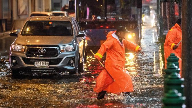 Petugas keamanan mengatur lalu lintas di jalan yang banjir saat hujan deras di Bangkok (23/9/2020). (AFP/Mladen Antonov)
