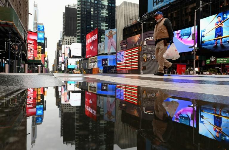 A man crosses the street at a nearly empty Times Square on April 09, 2020 in New York City