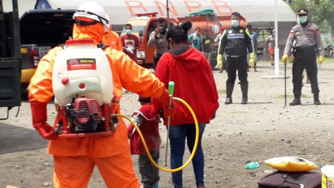 Ratusan penumpang KM Lambelu didisinfeksi sebelum memasuki gedung karantina, di Kabupaten Sikka, NTT. (Foto: Liputan6.com/Dionisius Wilibardus)