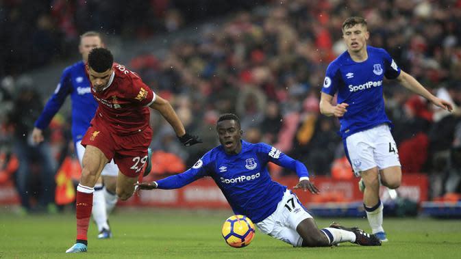 Gelandang Everton, Idrissa Gueye, terjatuh saat berusaha merebut bola dari striker Liverpool, Dominic Solanke, pada laga Premier League di Stadion Anfield, Minggu (10/12/2017). Laga bertajuk Derbi Merseyside itu berakhir imbang 1-1. (AP/Peter Byrne)