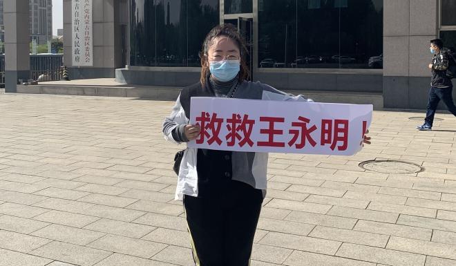 """Wang Ran hold a banner reading """"Save Wang Yongming"""". Photo: Handout"""