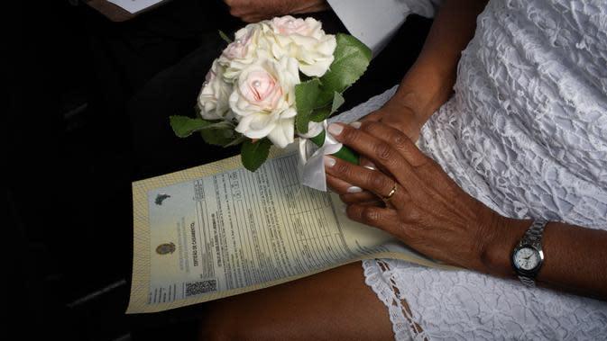 Mempelai wanita memegang buket bunga selama pernikahan drive-thru di kantor pencatatan sipil di Santa Cruz, Rio de Janeiro, Brasil, 28 Mei 2020. Fasilitas ini untuk memudahkan dan membantu pasangan yang ingin mengesahkan hubungan saat pandemi covid-19. (AP/Silvia Izquierdo)
