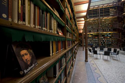 A book of Dutch master Rebrandt is displayed in the library which houses about one fifth of the total collection of books during a press preview of the renovated Rijkmuseum in Amsterdam, Thursday April 4, 2013. The Rijksmusuem, home of Rembrandt's Night Watch and other national treasures, is preparing to reopen its doors on April 13 2013 after a decade-long renovation. (AP Photo/Peter Dejong)