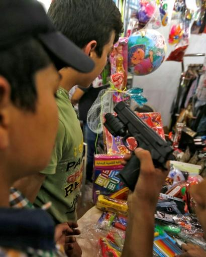 A boy holds a toy gun during a visit on May 13, 2018 to a government-sponsored market in Douma, on the outskirts of the capital Damascus