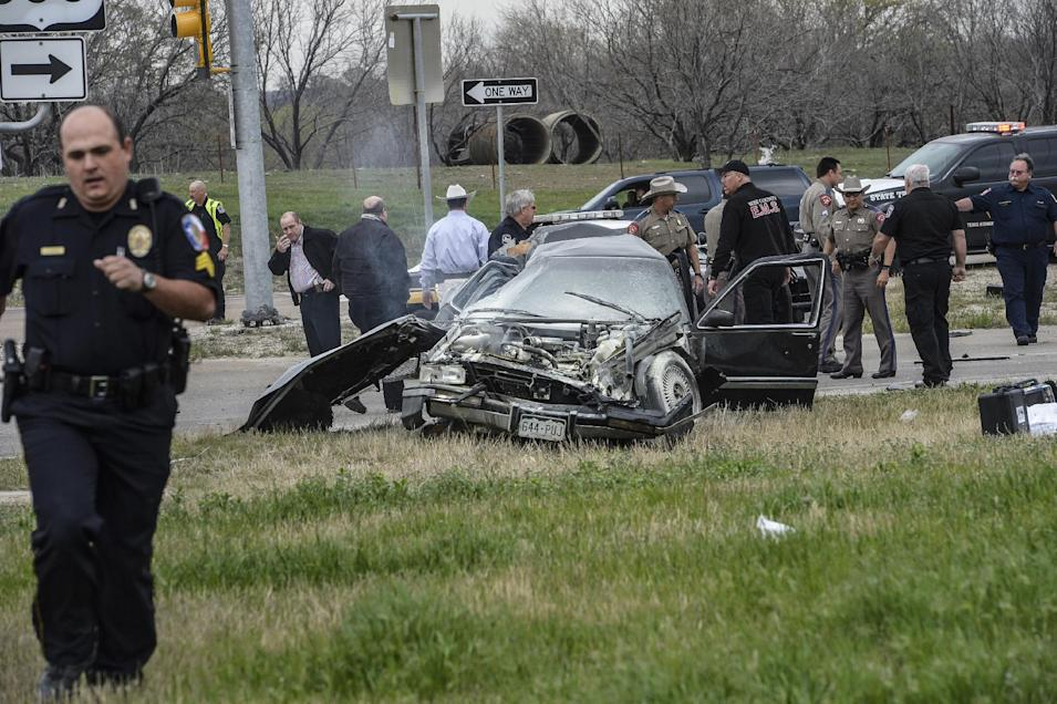 Emergency personnel are on the scene of a crash and shootout with police involving the driver of a black Cadillac with Colorado plates in Decatur, Texas, Thursday, March 21, 2013. The driver led police on a gunfire-filled chase through rural Montague County, crashed his car into a truck in Decatur, opened fire on authorities and was shot, officials said.  Texas authorities are checking whether the Cadillac is the same car spotted near the home of Colorado prisons chief Tom Clements, who was shot and killed when he answered the door Tuesday night. (AP Photo/Wise County Messenger, Joe Duty) MANDATORY CREDIT, MAGS OUT