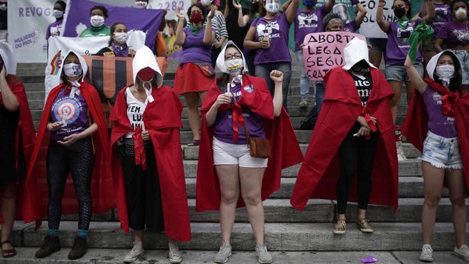 Pengunjuk rasa hak-hak aborsi berpakaian karakter meneriakkan slogan