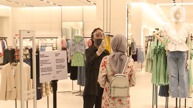 Petugas mengecek suhu pengunjung sebelum memasuki gerai pakaian di Mall Senayan City, Jakarta, Senin (15/6/2020). Pusat perbelanjaan atau mal di Jakarta kembali dibuka pada Senin (15/6) di masa PSBB transisi dengan jumlah pengunjung masih dibatasi hanya 50 persen. (Liputan6.com/Herman Zakharia)