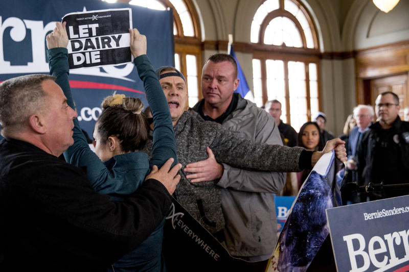 Democratic presidential candidate Sen. Bernie Sanders, I-Vt., at right, walks away as he is interrupted by protesters at a campaign stop at La Poste, Sunday, Jan. 26, 2020, in Perry, Iowa. (AP Photo/Andrew Harnik)