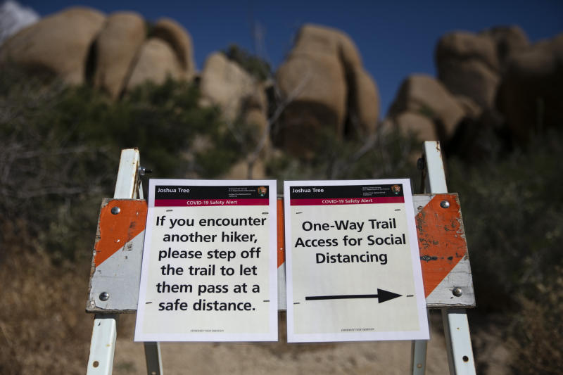 Signs advise visitors to social distance at Joshua Tree National Park in California, Tuesday, May 19, 2020. The park reopened this week after a lengthy closure to help slow the spread of the new coronavirus. (AP Photo/Jae C. Hong)