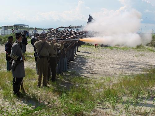 "Re-enactors representing both North and South fire a volley on Morris Island near Charleston, S.C., on Thursday, July 18, 2013 during a observance of the 150th anniversary of the charge of the black 54th Massachusetts Volunteer Infantry in a fight commemorated in the film ""Glory."" (AP Photo/Bruce Smith)"